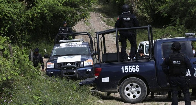 Federal police stand guard next to vehicles on a road at an area near clandestine graves at Pueblo Viejo, in the outskirts of Iguala, southern Mexican state of Guerrero
